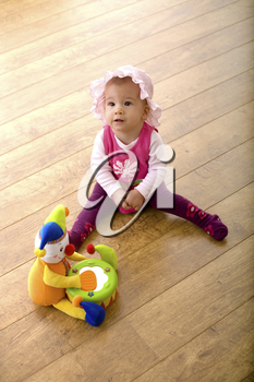 Baby girl (9 months) sitting on hardwood floor together with a toy clown. The toy is property released.