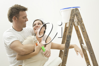 Happy couple painting their new home. Holding tools, hugging and smiling to each other.