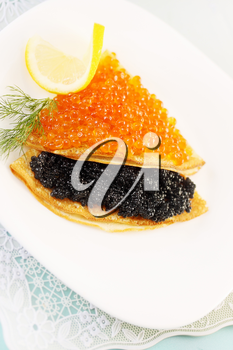 thin pancakes with red and black caviar