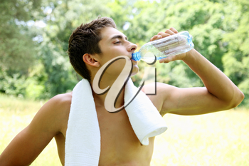 The young man drinks water from a bottle