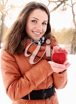 Young woman holding a red heart in the hands of