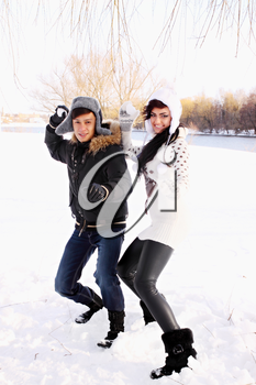 happy couple throwing snowballs in the park