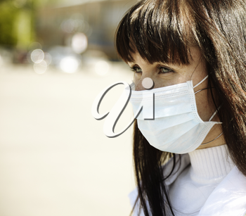 special toned photo f/x, real young woman with mask, selective focus on eye