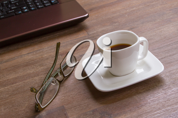 Espresso coffee with glasses on wood floor with laptop