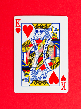 Old playing card (king) isolated on a red background