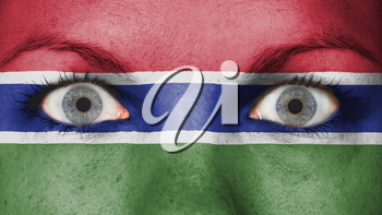 Close up of eyes. Painted face with flag of The Gambia