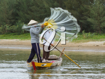 Fisherman is fishing with a large net in a river in Vietnam (Hoi An)