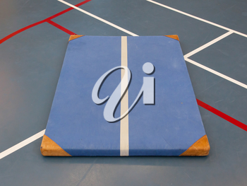 Very old blue mat on a blue court, school gym