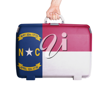 Used plastic suitcase with stains and scratches, printed with flag, North Carolina