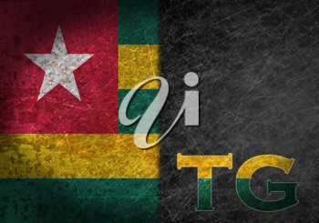 Old rusty metal sign with a flag and country abbreviation - Togo