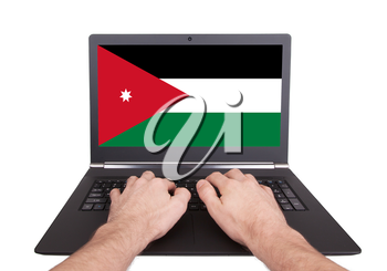 Hands working on laptop showing on the screen the flag of Jordan