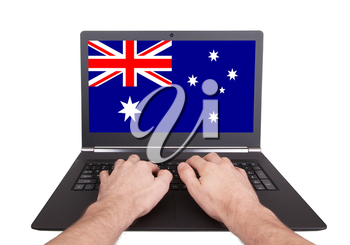 Hands working on laptop showing on the screen the flag of Australia