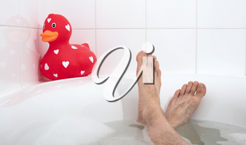 Men's feet in a bathtub, with large rubber duck, selective focus