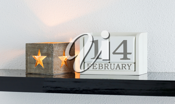 White block calendar present date 14 and month February on white wall background
