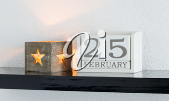 White block calendar present date 25 and month February on white wall background
