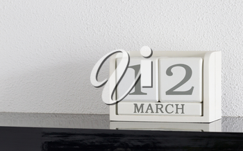 White block calendar present date 12 and month March on white wall background
