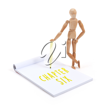 Wooden mannequin writing in a scrapbook - Chapter six