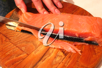 The image of hand cuts slices of a red fish