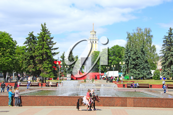people have a rest in city park with fountains in spring. city park in Gomel with beautiful view to fountains. City alley with path and fountains. Urban panorama. Eastern Europe. Travel concept
