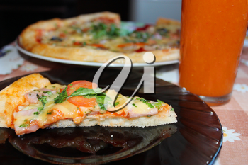 piece of tasty pizza on the plate and tomato juice