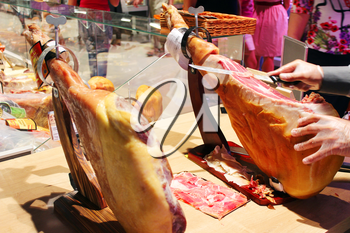 man cuts piece of fresh Jamon in the market