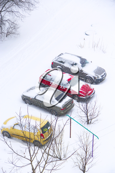 Parked cars covered with snow. Bad weather in town. Snowy day. Urban scene. Weather concept. Blizzard in city. Automobiles trapped in snow. Excessive precipitation in winter city