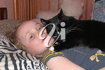 Little girl laying in bed together with her cat. Together with your pet. Black cat laying on its little mistress. Domestic pet