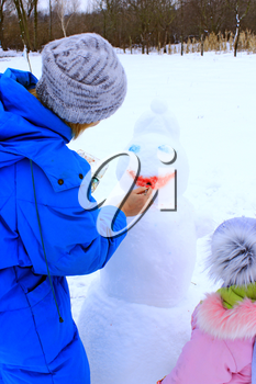 Mother and daughter paint snowman. Snowman face close up. Enjoying winter holidays. New Year attribute. Winter family vacations. Woman drawing smile for New Year snowman