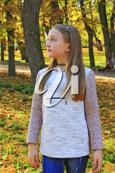 Young girl standing thoughtfully in autumn park with fallen yellow leaves. Girl in autumn park. Autumn weather. Girl resting in autumnal park. Yellow leaf cover