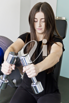 Brunette with long hair do exercise with dumbbells in gym