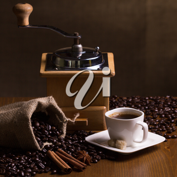 Still-life with coffee, cup with saucer, coffee mill, sac with beans and spices.