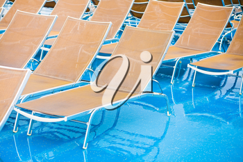 textile chairs on wet deck of cruise liner in rainy day