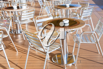 tables with ashtrays in outdoor bar on stern of cruise liner