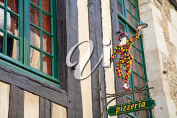 old wood harlequin figure under pizzeria on medieval house