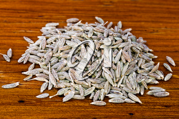 handful of dried cumin seeds on wooden table