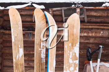 two pairs of wide wooden hunting skis and log house wall in winter day