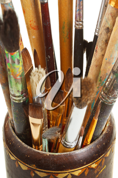 several used artistic paintbrushes in wooden cup closed up isolated on white background