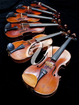 six violins with black background close up