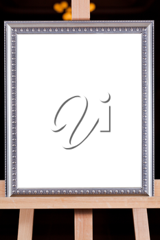 silver picture frame with white cut out canvas on easel