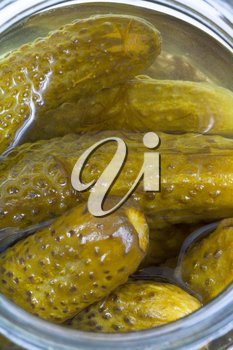 top view on pickled cucumbers in glass jar close up