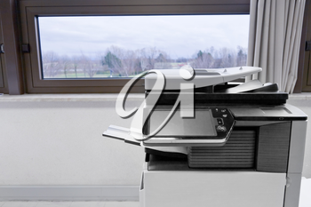 big grey copier in grey office and color life beyond window