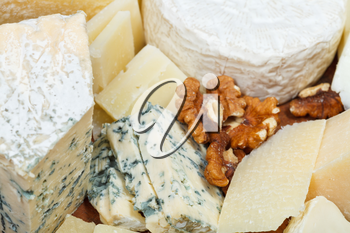 pieces of cheeses on wooden plate close up