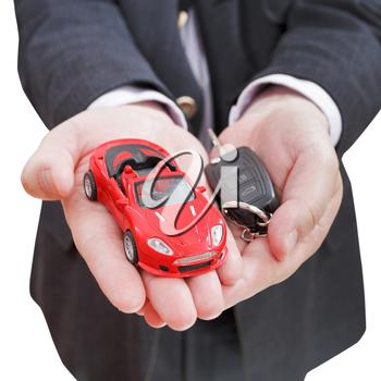 red car and key in seller's hand isolated on white background