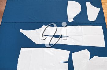 paper model of apparel on blue fabric for dress cutting