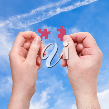 male and female hands with red puzzle pieces with blue sky background
