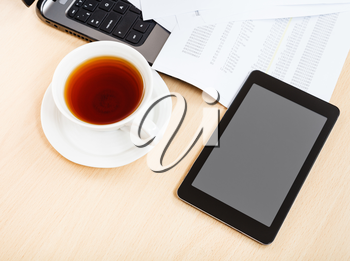 business workflow - above view cup of tea and tablet pc on office table