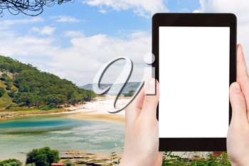travel concept - tourist photograph Cies Islands (illas cies) - Galicia National Park in Atlantic Ocean, Spain on tablet pc with cut out screen with blank place for advertising logo