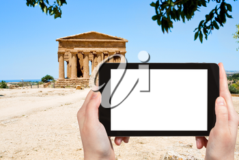 travel concept - tourist photograph ancient Temple of Concordia in Valley of the Temples, Agrigento, Sicily on tablet pc with cut out screen with blank place for advertising logo