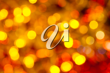 abstract blurred background - dark yellow and red flickering Christmas lights of electric garlands on Xmas tree