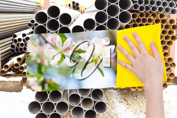ecology concept - hand deletes industrial landscape by yellow cloth from image and spring white blossoms are appearing